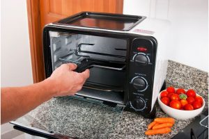 black and white color air fryer toster oven with bowl of tomatoes and carrots