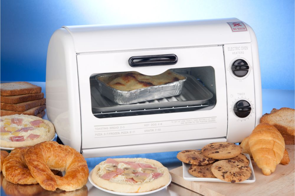white toaster oven surrounding with pizza, cookies, and croissant